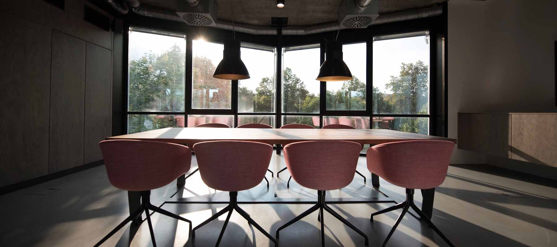 a boardroom of eight chairs and a long table overlooking large windows with a view