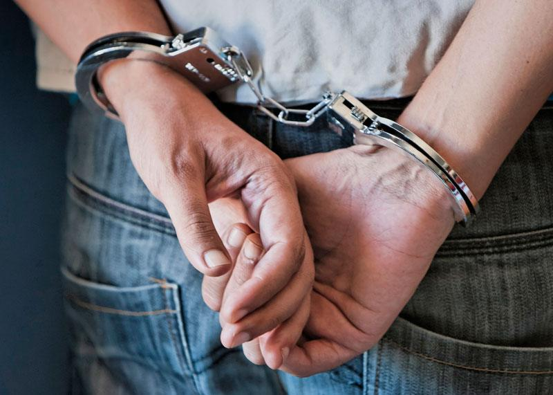 man's hands in handcuffs behind his back
