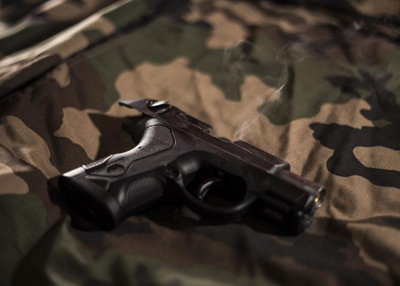 a handgun laying on army sheets